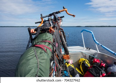 TAIPALSAARI, FINLAND - JULY 2, 2015: Touring bikes tied to a fishing boat with panniers on the boat floor by the lake Saimaa, Finland for crossing to the other side of the lake from Taipalsaari.