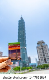 Taipei 1 day pass card in hand with blurred Taipei 101 landmark building background, makes traveler convenience and save for public metro transport, Taiwan Taipei 12 May 2019
