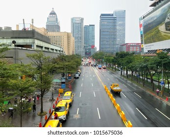 Taipei 30 January 2018 ; In the evening of a rainy day in Taipei city center. Taxis are queuing near office building and shopping mall while people crossing the road during traffic light.