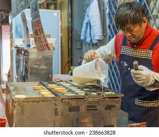 TAIPEI CITY, TAIPEI, TAIWAN. DECEMBER 17, 2014.  Vendor making cartwheel pies at Shida night market