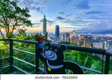 Taipei City, Taiwan-August 30, 2017: Landscape Night View Of Taipei City With Bravo the Bear (2017 Universiade Mascot) and Taipei 101 from The Top of Elephant Mountain