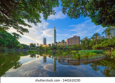 Taipei park garden and reflection of skyscrapers buildings. Financial district and business centers in smart urban city at noon, Taiwan.