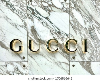 Taipei, Taiwan - 04/14/2020: Illuminated Gucci sign on a marble wall. Gucci is an Italian fashion and leather goods brand founded by Guccio Gucci in Florence in 1921.