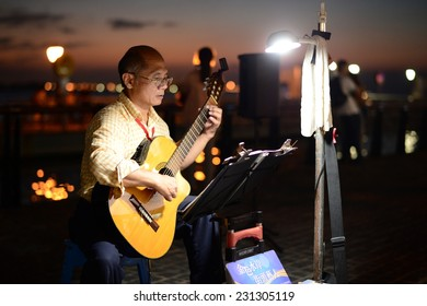Taipei, Taiwan - 9 Nov, 2014: Unidentified Street Performer who playing classical guitar at riverside of Tamsui in Taipei. It is a destination for tourists to enjoy food and sunset along riverside.