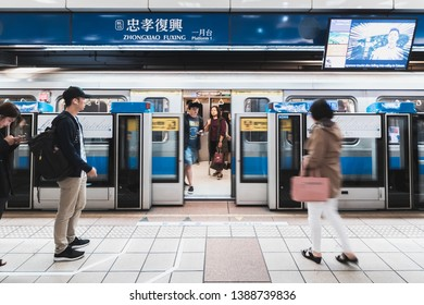 Taipei, Taiwan - April 13, 2019: Crowd of people queue up to ride a metro train with opening metro train door in the background