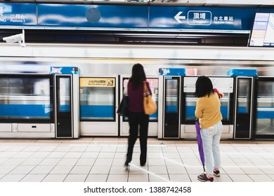Taipei, Taiwan - April 13, 2019: People waiting for the next metro train on Bannan Line (Blue Line) as one is leaving in motion blur
