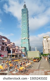Taipei, Taiwan - April 26, 2019: Scenic rows of orange YouBikes on Xinyi Road. Bicycle parking station of the Taipei Bike Sharing System. Awesome view of Taipei 101. Fabulous cityscape.