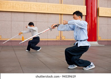 Taipei, Taiwan - August 13, 2011: Two men crouch, legs crossed in synchronized Tai Chi Chuan stance. Tai Chi is a martial arts popular in Chinese culture for its health effects