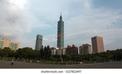 TAIPEI, TAIWAN - CIRCA AUGUST 2019 : Cityscape of Taipei. View of Taipei 101 building and national flag of Taiwan. Shot from Sun Yat-Sen Memorial Park.