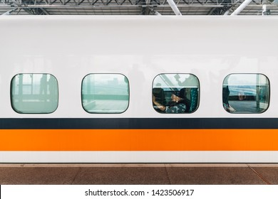 TAIPEI, TAIWAN. DEC 27, 2017: Side view of Taiwan High Speed Train, White train with orange and blue stripe with passengers sitting near window stop on platform in Taiwan, Taipei.