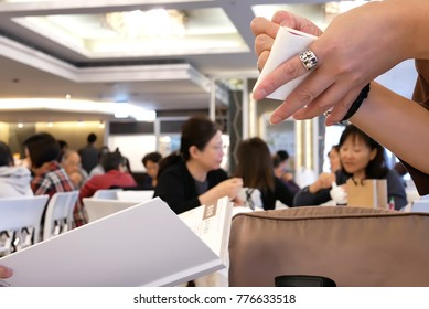 Taipei, Taiwan - December 01, 2017 : Motion of waitress taking customer order with people enjoy meal inside restaurant