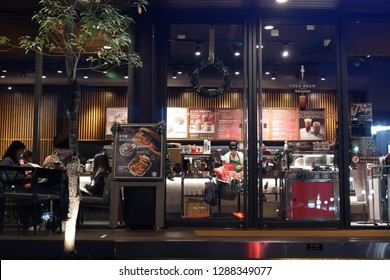 Taipei, Taiwan - December 01, 2018 : Motion of people enjoying coffee inside Starbucks coffee at night.
