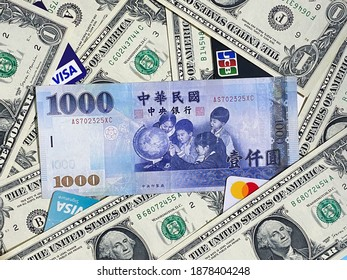 Taipei, Taiwan - December 17, 2020 : Taiwan one-thousand-dollar money surrounding by US one-dollar money. Some credit cards hide in money. Concept for current exchange rate, foreign currency exchange.
