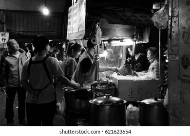 Taipei, Taiwan - February 22, 2017: Locals perusing and enjoying one of the many street stalls that open till late on the streets of Taiwan.