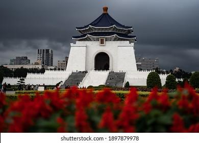 TAIPEI, TAIWAN - FEBRUARY 4, 2020: Chiang Kai-shek Memorial Hall, Taipei and surrounding gardens with red flowers and a dark sky.