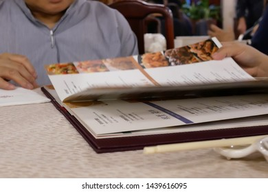 Taipei, Taiwan - January 05, 2019 : Motion of woman looking at menu inside Chinese restaurant