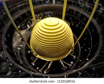 Taipei, Taiwan - January 1, 2015 : Tourists observe the world's largest tuned mass damper in Taipei 101. The device is used to reduce unwanted vibration from wind and earthquakes.