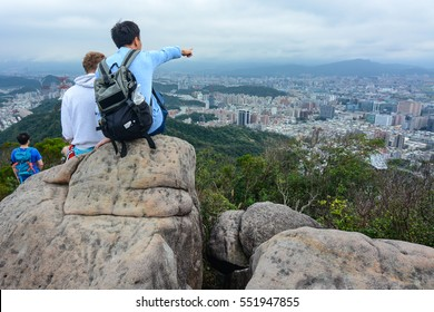 TAIPEI, TAIWAN - JANUARY 8, 2017 - Young Taiwanese man pointing out important landmarks and history of Taipei for a foreign student studying abroad