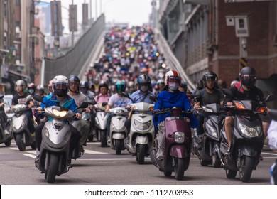 Taipei, Taiwan - June 13, 2018: Motorcycles go down the Taipei bridge during rush hour in the morning.