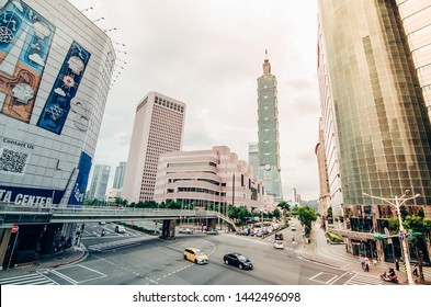 Taipei, Taiwan - May 15, 2019:View of a busy street corner in Downtown Taipei City at rush hour with cars & buses dashing by, Taipei 101 Tower & World Trade Center Building in Xinyi Financial District