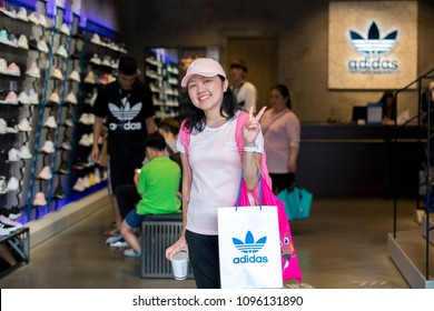 Taipei, Taiwan - May 19, 2018 : A girl wearing Adidas carrying backpack of Adidas and holding a shopping bag Adidas at Adidas original shop Ximending street in Taipei, Taiwan