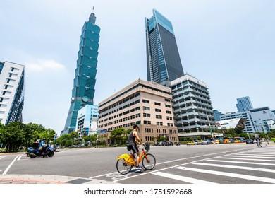 Taipei, Taiwan- May 4, 2020: People are riding public bikes crossing the road nearby Taipei 101 skyscraper. in Xinyi District Taipei, Taiwan.