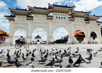 Taipei, Taiwan - November 06, 2018: Woman rides a bycicle in front of the National Chiang Kai-shek Memorial Hall on November 06, 2018 in Taipei, Taiwan.
