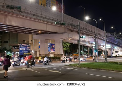 Taipei, Taiwan - November 30, 2018 : Motion of commuters and cars passing by road at night