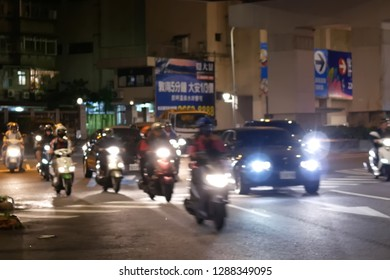 Taipei, Taiwan - November 30, 2018 : Blur motion of commuters and cars passing by road at night