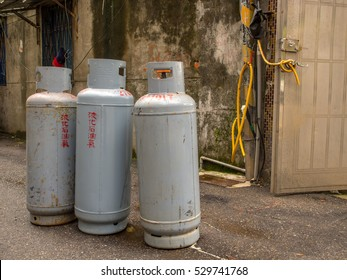 Taipei, Taiwan - October 08, 2016: Gray, metallic gas cylinders with a damaged wall of a brick building in a background