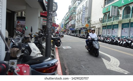 Taipei, Taiwan - October 26, 2015 : A lot of small motorcycles, scooters and  mopeds parking along the road side at Zhongzheng District