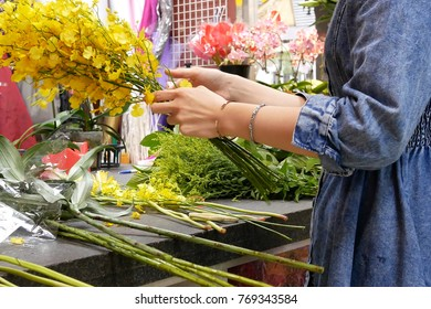 Taipei, Taiwan - October 29, 2017 : Motion of florist prepares a bouquet of flowers for customer, close up on hand.