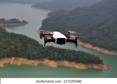 TAIPEI, TAIWAN - September 2, 2018: A DJI mavic air drone in mid-air flying over a green reservoir. DJI mavic air is the latest hobby drone by DJI.