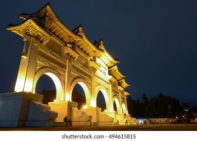 """TAIPEI, TAIWAN - SEPTEMBER 8, 2016: Night lights shine on the gated entrance to Liberty Square in Taipei. The Chinese text says: """"Liberty Square""""."""