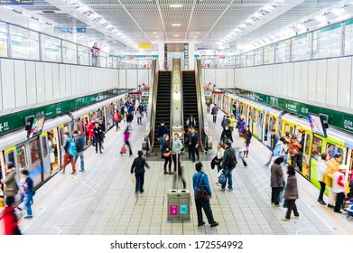 TAIPEI,TAIWAN - JANUARY 19: Passengers waiting and ride the MRT, on January 19,2014 in Taipei. The (Metropolitan Rapid Transit) MRT serves 240,000 people daily with 109 stations and 121 km of track.