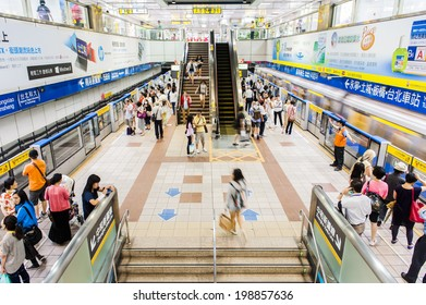 TAIPEI,TAIWAN - JUNE 14: Passengers waiting and ride the MRT, on June 14,2014 in Taipei. The (Metropolitan Rapid Transit) MRT serves 240,000 people daily with 109 stations and 121 km of track.