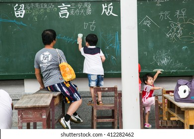 Taipei/Taiwan - June 19 2014: A man is teaching his young son how to write on the board.