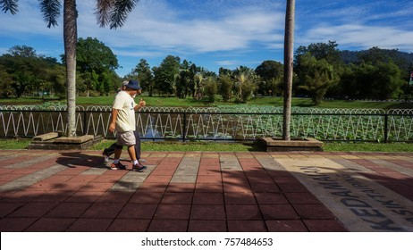 TAIPING LAKE IN PERAK, MALAYSIA - November 2017: Two good friends walk at Beautiful Taiping lake located in Malaysia and became a place of leisure and tourist attractions.
