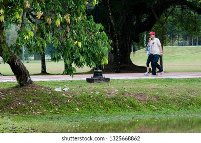 Taiping, Perak , Malaysia - March 26, 2016: Group of People picnicking under a big tree at Taiping Lake Park. Some of the are using wheelchair and bicycle.