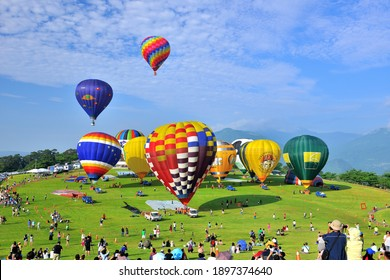 Taitung County, Taiwan-May 31, 2014: People on the grassland and hot air balloons flying freely.
