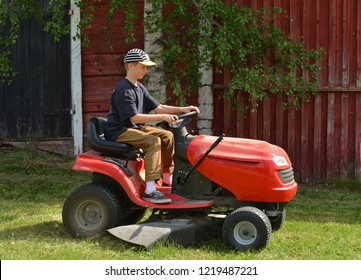 TAIVALKOSKI, FINLAND - JULY 14, 2018: Happy boy mows on riding mower green grass in meadow