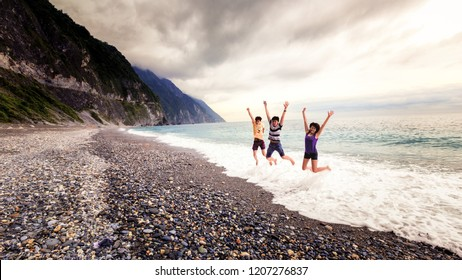 TAIWAN - HUALIEN - MAY 2013: A group of unidentified young people jumps on the beach of taiwan. Dramatic mountain landscapes to white-sand beaches, Taiwan is a land of countless pleasant surprises.