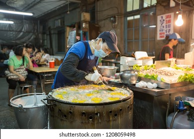 TAIWAN, HUALIEN - MAY 2013: An unidentified stall vendor preparing oyster omelet at her food stall. This favorite night market snack is as much about its abundance of textures as it is about flavor.