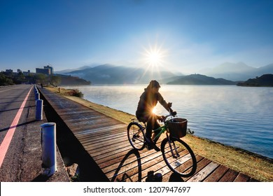 TAIWAN, SUN MOON LAKE - JANUARY 2015: A unidentified man cycles across Sun Moon Lake. Taiwan's largest lake, Sun Moon Lake is located in the mountains of Nantou at the geographic centre of Taiwan.