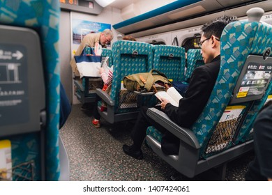 TAIWAN, TAIPEI. DEC 27, 2017: A man wearing suit reading and sitting in Taiwan High Speed Rail (THSR) in the morning in Taiwan, Taipei.