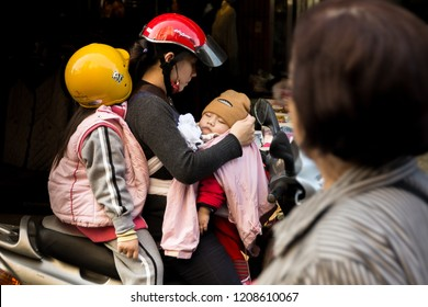 TAIWAN, TAIPEI - JANUARY 2014 : Family with two children on a motorcycle, mother and her children. Transport in Asia. Taiwan. Mother takes care of her children. Mother protects her child. Road safety.