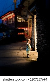 TAIWAN, TAIPEI, JIUFEN - MAY 2013: An unidentified young boy curiously looks into a stall on street of famous tourist attraction in Jiufen, Taiwan.