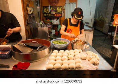 TAIWAN, TAIPEI - MAY 2013: A unidentified woman prepares handmade taiwanese meat bun for sale at her stall. Many locals open stall to sell their specialty, making taiwan a great destination for food.