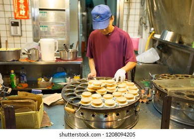 TAIWAN, TAIPEI - MAY 2013: A unidentified man prepares tasty pancake for sale at his stall. Many locals open stall to sell their specialty, making taiwan a great destination for food.