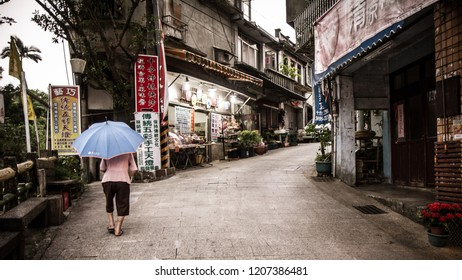 TAIWAN, TAIPEI, SHIFEN - AUGUST 2012: A asian hunchback elderly old woman carries an umbrella and pushes herself to climb a gentle slope up along the street of Shifen, Taiwan.